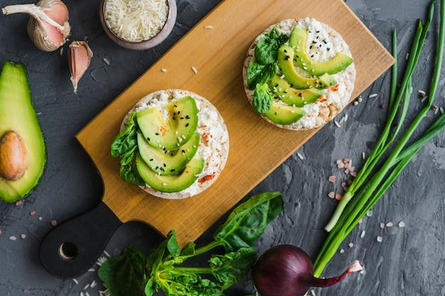 Délicieux gâteau de riz au fromage à la crème et avocat sur une planche en bois avec des légumes biologiques