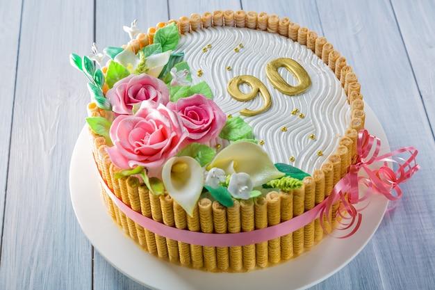 Délicieux gâteau avec des roses, des lis, des feuilles et des personnages 90 ans sur une table en bois bleu clair