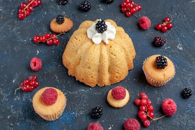 Délicieux gâteau sucré avec des baies et de la crème délicieuse avec des canneberges réparties sur un bureau sombre, biscuit gâteau aux baies