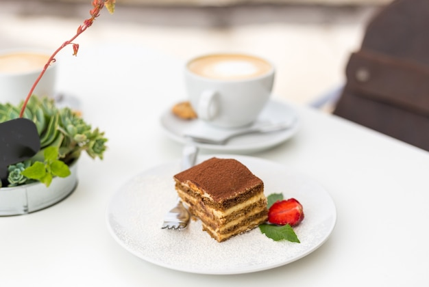 Délicieux gâteau tiramisu aux fraises fraîches et à la menthe sur une assiette sur fond blanc. petit-déjeuner avec une tasse de café au café