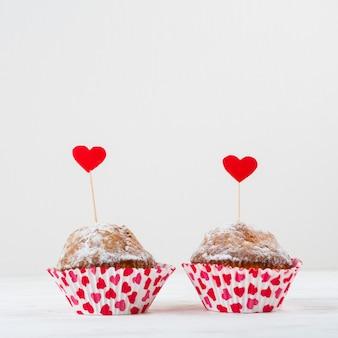 Délicieux gâteaux avec des cœurs sur des baguettes