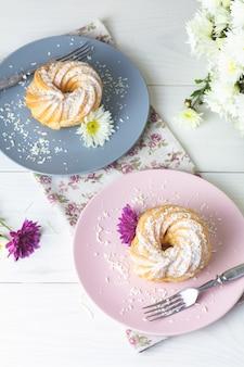 Délicieux gâteaux avec des copeaux de noix de coco sur une plaque rose et grise sur un tableau blanc