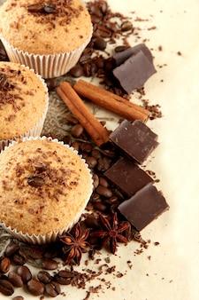 Délicieux gâteaux muffins au chocolat, épices et graines de café, sur fond beige