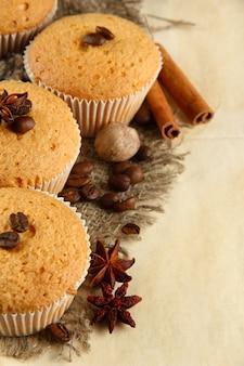 Délicieux gâteaux muffins sur toile de jute, épices et graines de café, sur fond beige