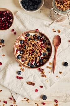 Délicieux granola végétalien sain avec des noix de pécan dans un bol fruité avec du yaourt sur un tableau blanc