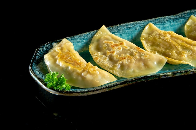 Délicieux gyoza asiatique poêlé farci de viande, servi sur une assiette bleue.