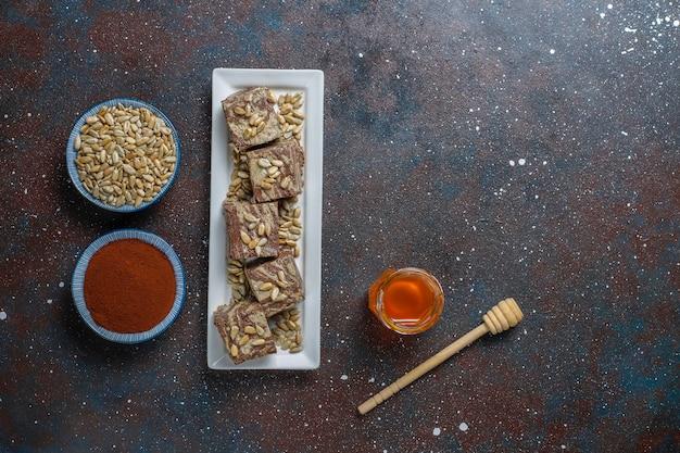 Délicieux halva en marbre avec des graines de tournesol, de la poudre de cacao et du miel, vue de dessus