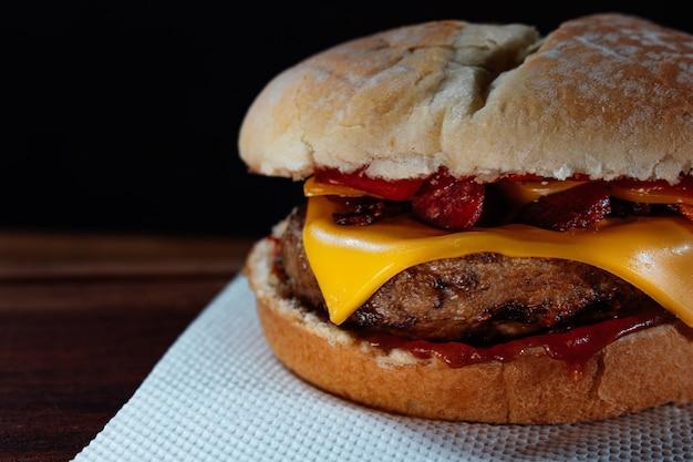 Délicieux hamburger au bacon et fromage cheddar sur du pain fait maison avec des graines et du ketchup sur une surface en bois et un fond noir.