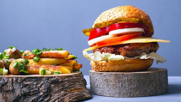 Délicieux hamburger avec des côtelettes de viande, des légumes et du fromage avec un petit pain doux, des frites et des champignons champignon saupoudrés d'oignons verts sur des sous-verres en bois de la forêt sur un fond gris.