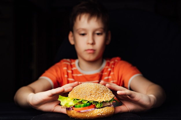 Délicieux hamburger dans les mains du garçon.