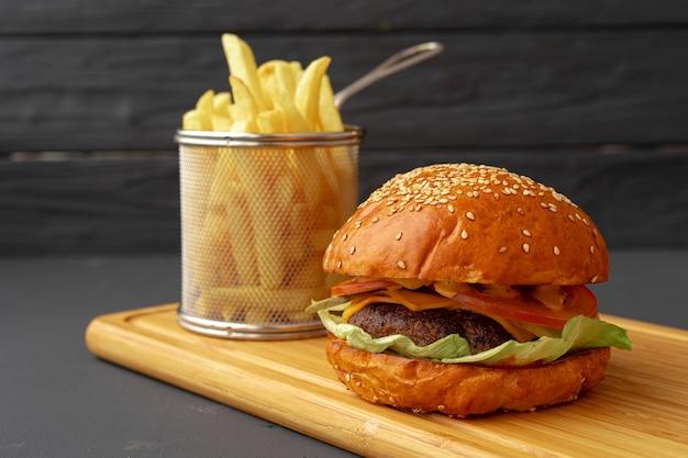 Délicieux hamburger et frites sur planche de bois sur fond noir