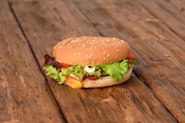 Délicieux hamburger juteux avec salade verte sur une table en bois