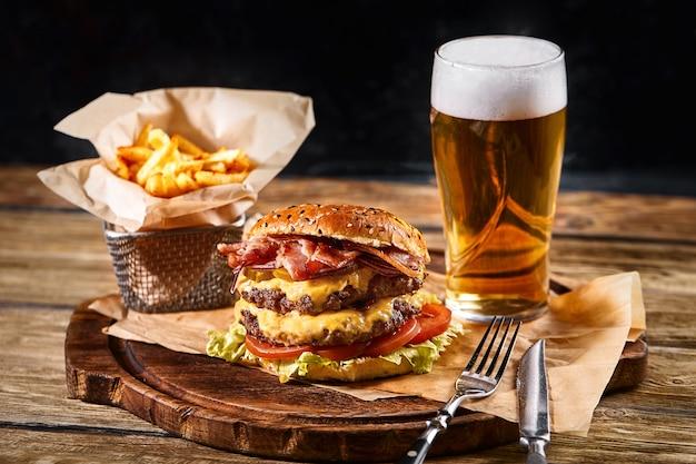 Délicieux hamburger noir épicé chaud avec du piment et un verre de bière sur une planche à découper sur une table en bois blanc
