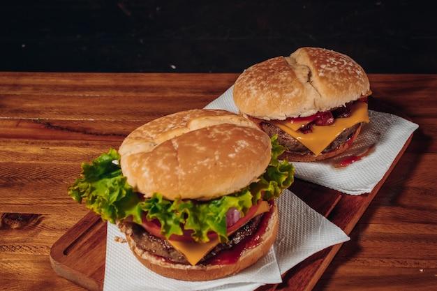 Délicieux hamburgers au bacon et fromage cheddar et avec de la laitue, tomate et oignon rouge et bacon et cheddar sur du pain fait maison avec des graines et du ketchup sur une surface en bois et un fond noir.