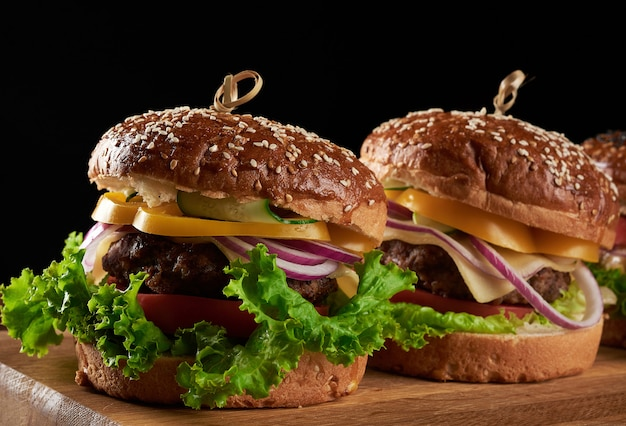 Délicieux hamburgers avec escalope de boeuf frite, tomate, laitue et oignons, farine de blé blanc croustillant
