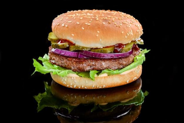 Délicieux hamburgers grillés faits maison avec du bœuf. sur fond noir