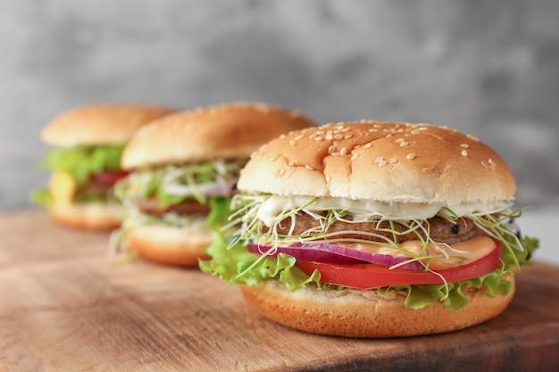 Délicieux hamburgers sur planche de bois