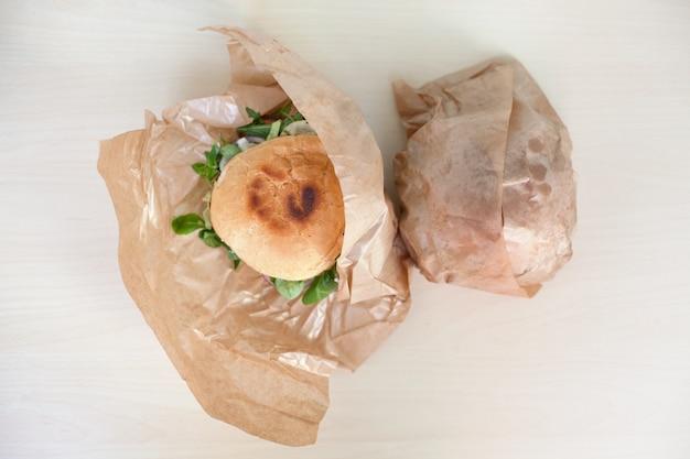 Délicieux hamburgers avec une salade dans une boîte en papier sur une table