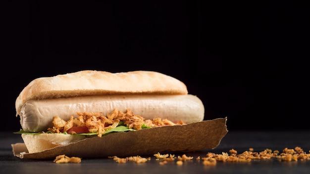 Délicieux hot-dog de restauration rapide sur papier sulfurisé vue de face