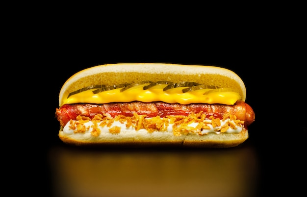 Délicieux hot-dog avec saucisse au bacon, mayonnaise avec chips d'oignon, sauce au fromage et cornichons.
