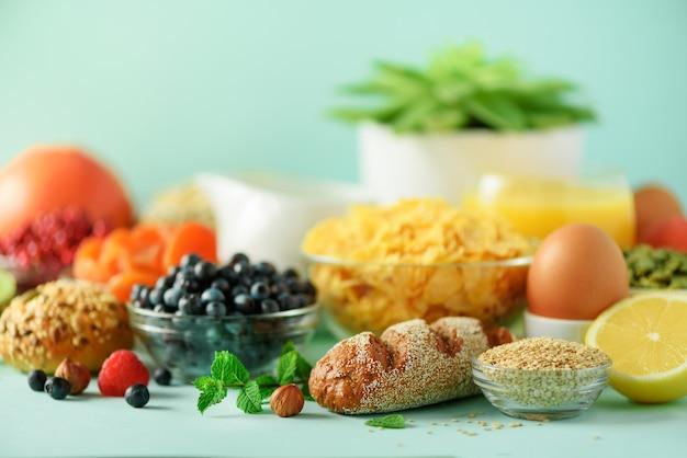 Délicieux ingrédients du petit déjeuner. œuf à la coque, flocons d'avoine, noix, fruits, baies, lait, yaourt, orange, banane, pêche