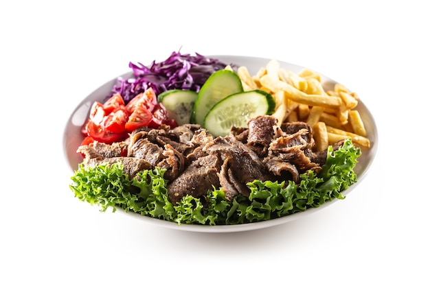 Délicieux kebab de veau turc isolé servi sur une assiette blanche avec de la laitue verte fraîche, des tomates juteuses, du chou, du concombre et des frites croustillantes et salées.