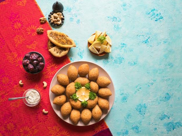 Délicieux kibbeh frit avec sauce au yogourt dans un bol servi sur une assiette sur une table bleue. recette libanaise classique.