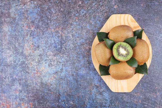 Délicieux kiwi entiers et tranchés avec des feuilles placées sur une assiette en bois.