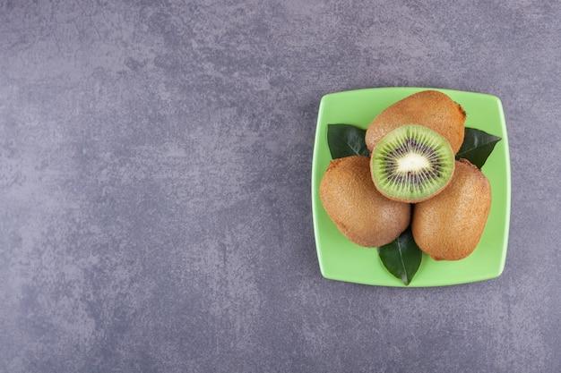Délicieux kiwi entiers et tranchés avec des feuilles placées sur une assiette verte.