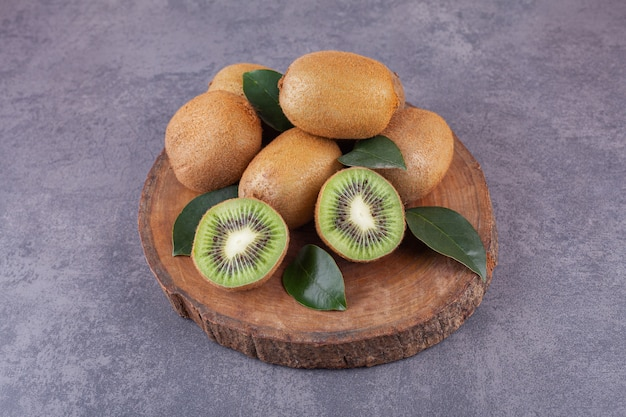 Délicieux kiwi entiers et tranchés avec des feuilles placées sur un morceau de bois.