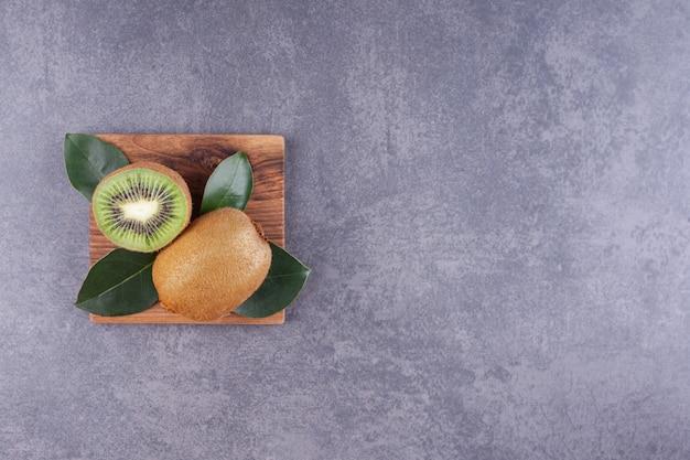 Délicieux kiwi tranché avec des feuilles placées sur une assiette en bois.