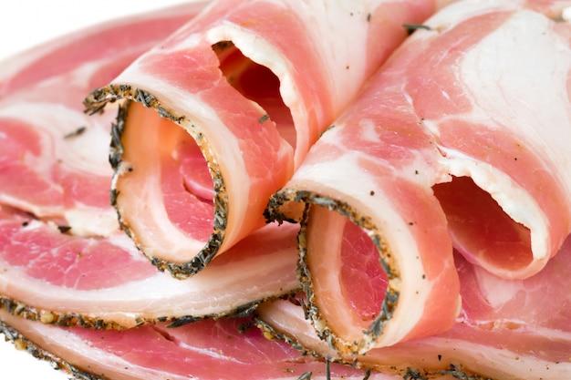 Délicieux lard en tranches, bacon de porc, viande, jamon, prosciutto sur blanc, gros plan