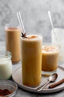 Délicieux latte d'automne aux épices de citrouille avec du lait fouetté. boisson chaude à la cannelle et paille de verre.