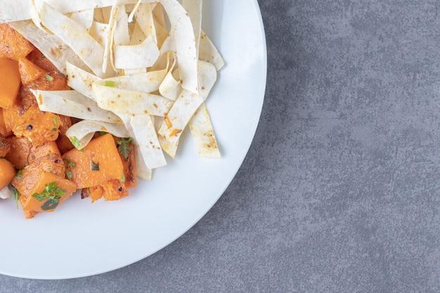 Délicieux lavash en tranches et carottes cuites au four dans une assiette, sur la surface en marbre.