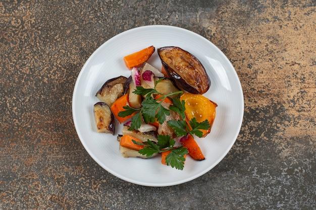 Délicieux légumes grillés sur plaque blanche.