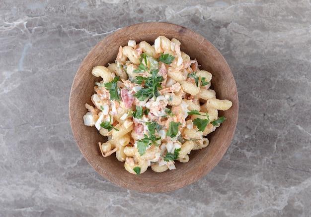 Délicieux macaronis avec salade mixte dans un bol en bois.