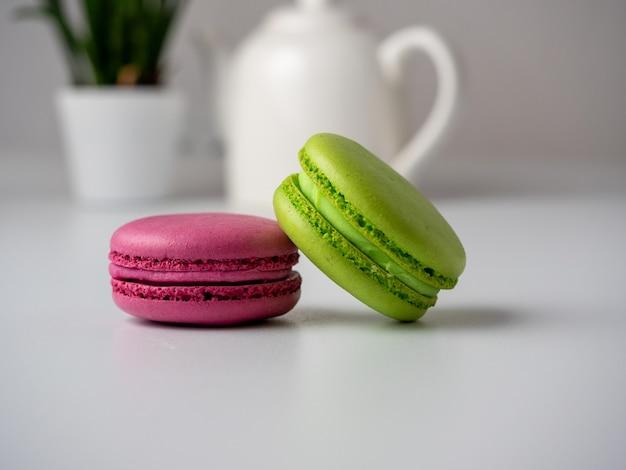De délicieux macarons colorés se trouvent sur une table blanche. en arrière-plan, une théière blanche et une fleur