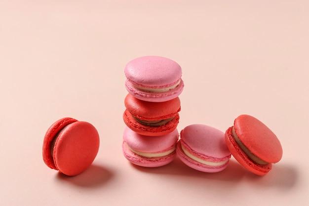 Délicieux macarons sucrés sur fond rose, macarons rouges et roses, concept pour la saint-valentin, anniversaire, 8 mars et fête des mères