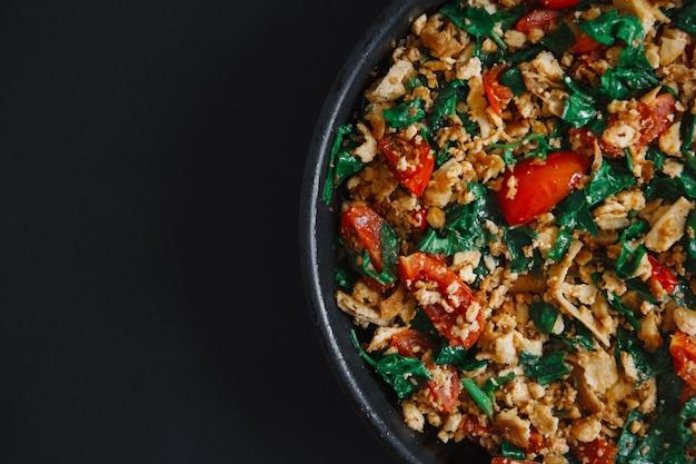 Délicieux mélange de légumes poêlés avec du tofu végétarien faible en gras sur fond noir