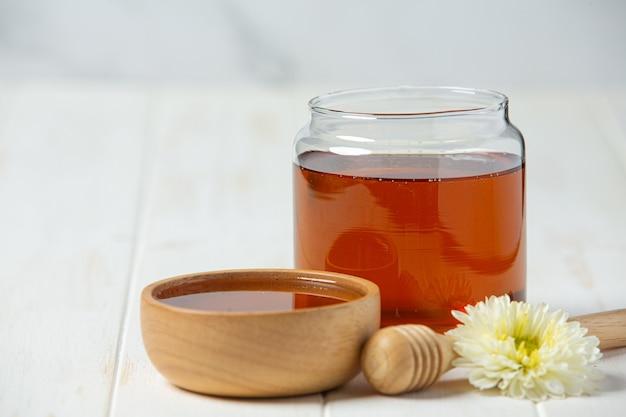 Délicieux miel sur une surface en bois blanche