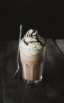 Délicieux milk-shake crémeux avec cookie sur table en bois