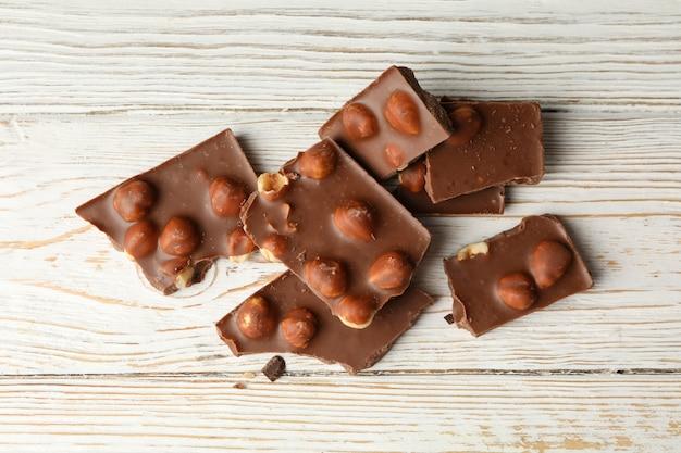 Délicieux morceaux de chocolat sur une table en bois blanc
