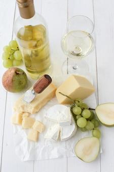 Délicieux morceaux de fromage, fruits et vin blanc