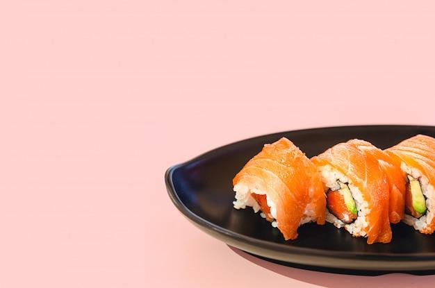Délicieux morceaux de saumon et sushi avocat sur une plaque avec fond rose et espace copie