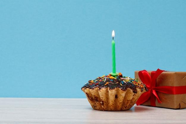 Délicieux muffin d'anniversaire avec glaçage au chocolat et caramel, décoré d'une bougie festive brûlante et d'une boîte-cadeau sur fond bleu. concept minimal de joyeux anniversaire.