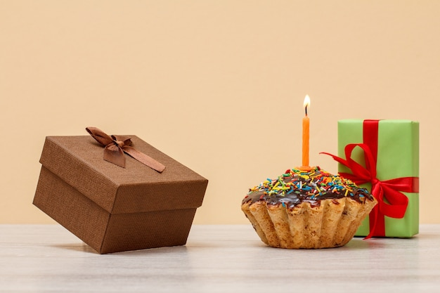 Délicieux muffin d'anniversaire avec glaçage au chocolat et caramel, décoré de bougies festives brûlantes et de coffrets cadeaux sur fond beige. concept minimal de joyeux anniversaire.