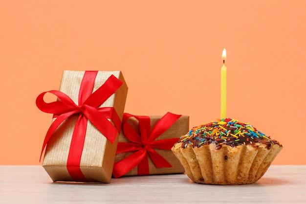 Délicieux muffin d'anniversaire avec glaçage au chocolat et caramel, décoré de bougies festives brûlantes et de coffrets cadeaux sur fond orange. concept minimal de joyeux anniversaire.