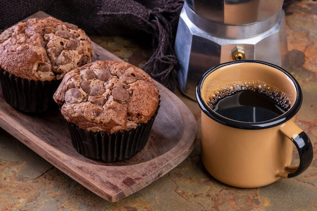 De délicieux muffins au chocolat, une tasse à café et une cafetière italienne traditionnelle.