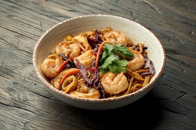 Délicieux nourriture de rue asiatique - nouilles aux œufs aux crevettes, coriandre, légumes et œufs brouillés dans un bol blanc sur une surface en bois