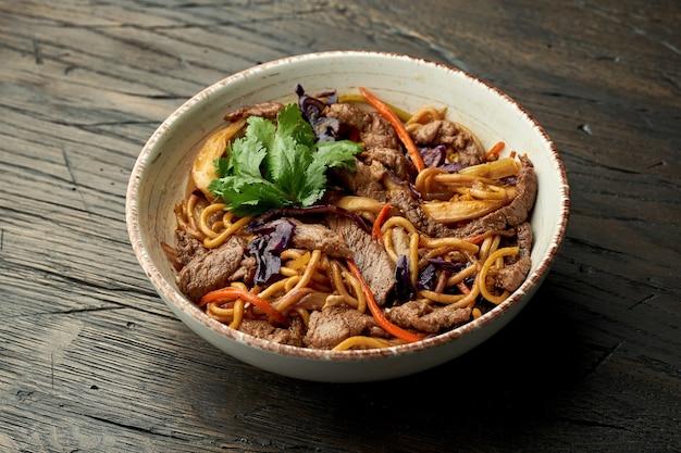 Délicieux nourriture de rue asiatique - nouilles aux œufs avec du boeuf, coriandre, légumes et œufs brouillés dans un bol blanc sur une surface en bois